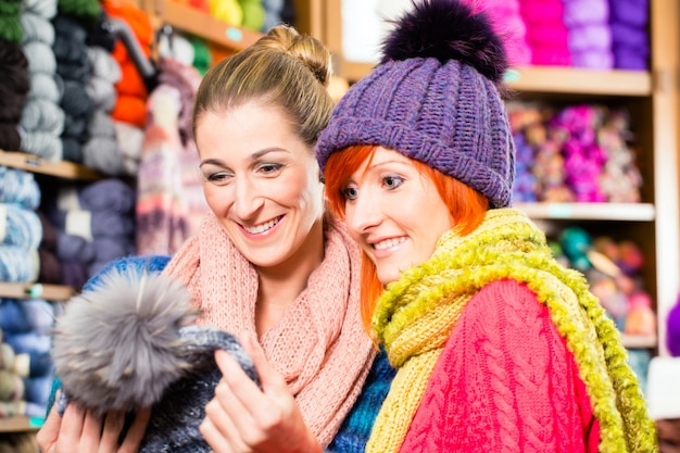Young women in knitting shop shopping fashion