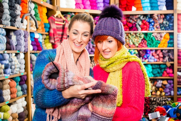 Young women in knitting shop shopping pullover