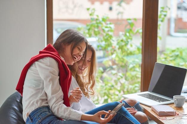 Молодые женщины счастливо смеются, принимая селфи