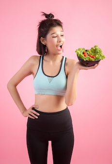Young women like to eat vegetables on a pink.