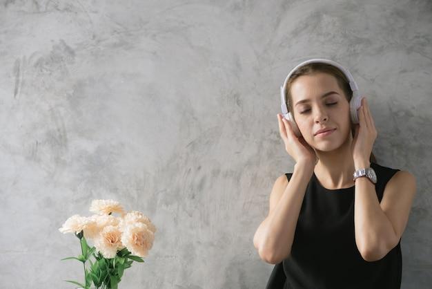若い女性は思っている間音楽を聞いて、女性は現代の宿題で宿題をし、女性は幸せな感情のコンセプトで働いています。ヴィンテージエフェクトスタイルの写真。