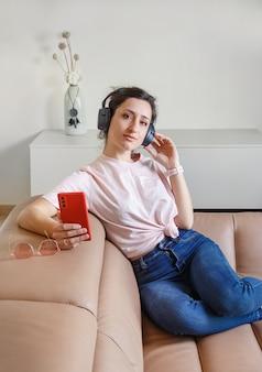 집에서 베이지 색 소파에 앉아있는 동안 손에 휴대 전화로 헤드폰으로 음악을 듣는 젊은 여성