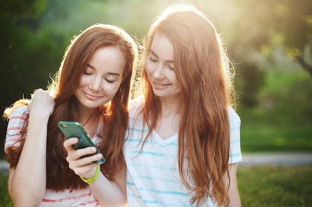 스마트 폰보고 젊은 여성. 휴대 전화에서 소셜 미디어를 스크롤하는 두 생강 자매. 무선 통신은 우리의 미래입니다. 라이프 스타일 개념.