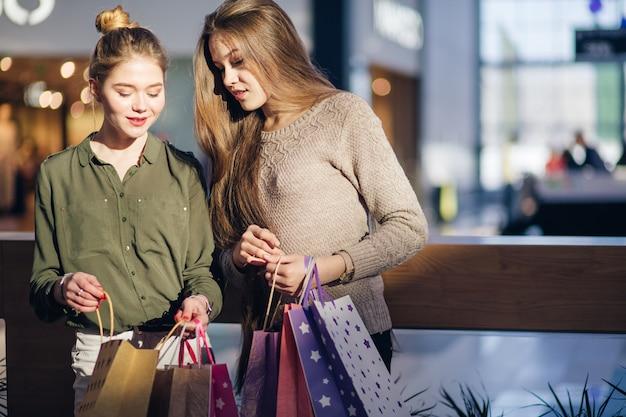 ショッピングモールでの訪問後に買い物袋を探している若い女性