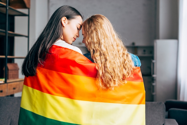 Young women in love covering in rainbow flag