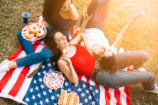 Giovani donne che si trovano sulla bandiera americana