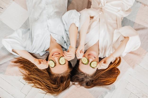 若い女性はキュウリのスライスで自家製の顔の美しさのマスクを作ります
