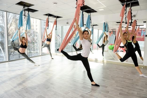 グループで反重力ヨガの練習をしている若い女性