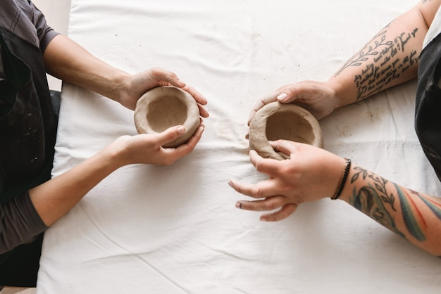 Young women making earthen pot in pottery workshop