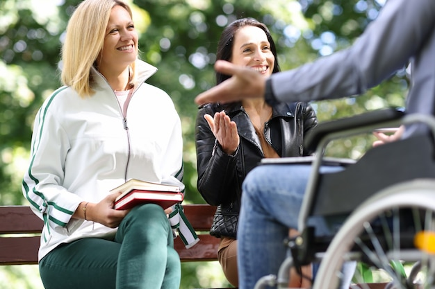 Young women and man in wheelchair laugh and chat in park social life of disabled people concept