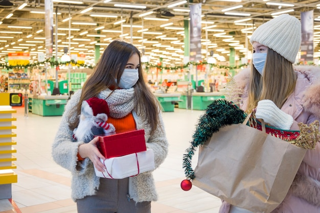 Young women in medical mask shopping for christmas in mall.