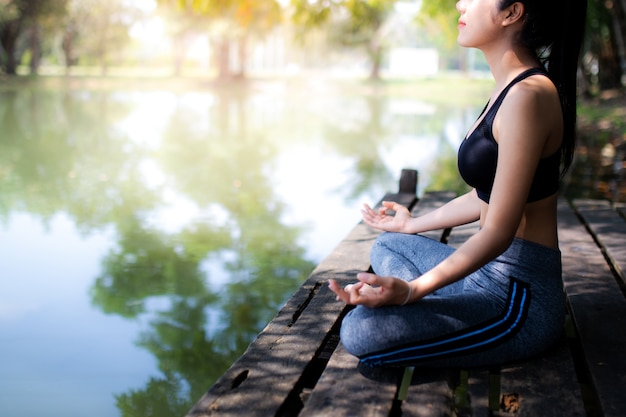 Young women meditate while doing yoga in atmosphere peaceful