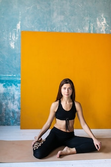 요가 클래스에서 명상하는 젊은 여성. 여자 연습 스트레칭 운동을 교차 다리와 피트니스 매트에 앉아.