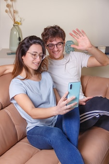 Young women and men have a videocall with cell phone while sitting on the beige sofa at home.