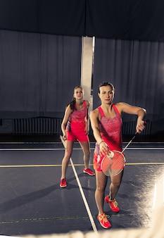 Молодые женщины играют в бадминтон в тренажерном зале