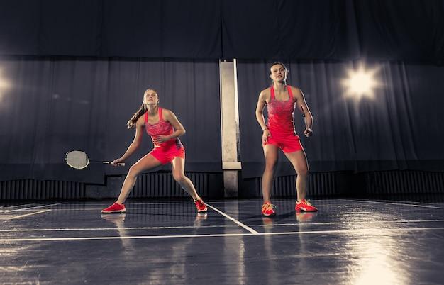 Giovani donne che giocano a badminton in palestra