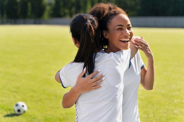 サッカーチームで遊ぶ若い女性