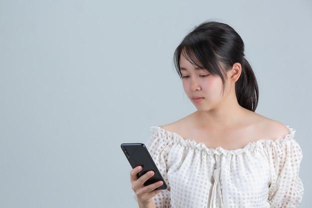 灰色の壁に電話で遊ぶ若い女性