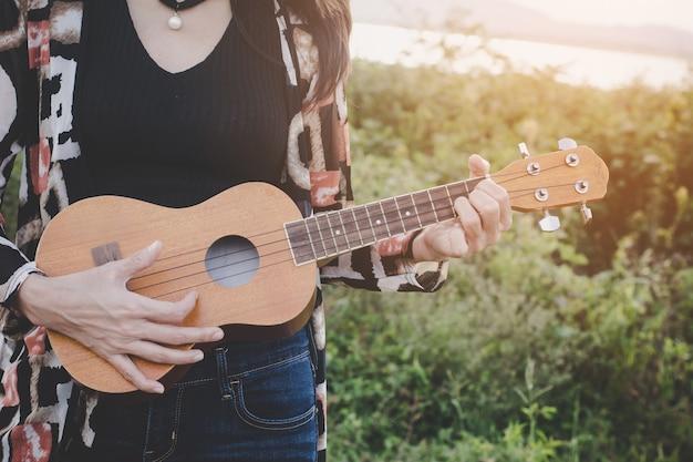 Young women playing on ukulele