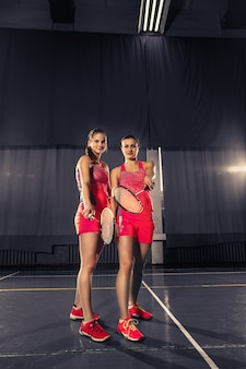 Young women posing after playing badminton at gym
