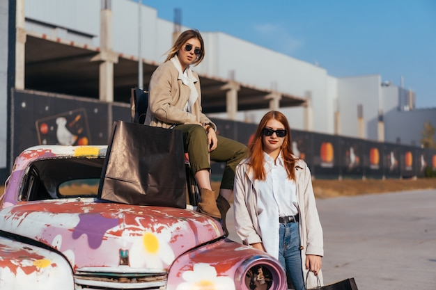 Giovani donne in posa vicino a una vecchia automobile decorata