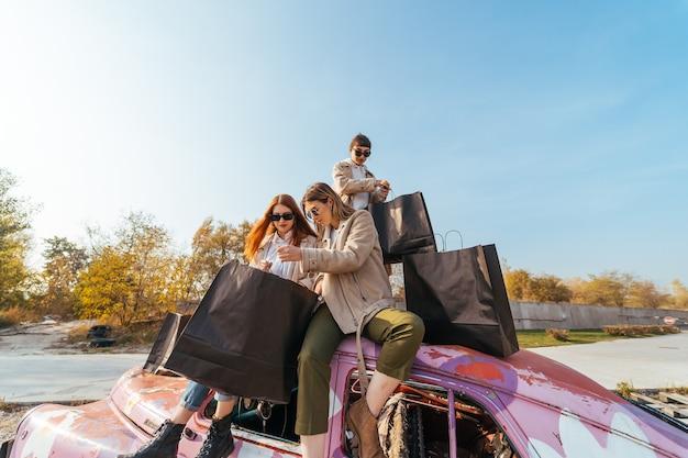 Giovani donne in posa sulla vecchia automobile decorata