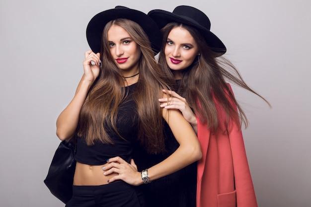 Giovani donne in posa e indossando cappelli neri alla moda