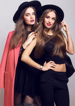 Young women posing and wearing stylish black hats