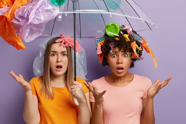 Young women posing with garbage on them