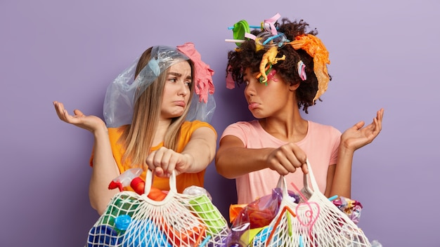 Молодые женщины позируют с пластиковыми отходами