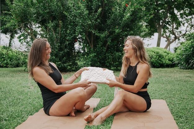 Молодые женщины занимаются йогой в парке, сидя на циновках на лужайке, улыбаются друг другу. йога в концепции парка. концепция обучения
