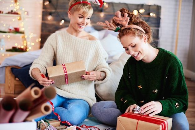 Молодые женщины готовят рождественские подарки