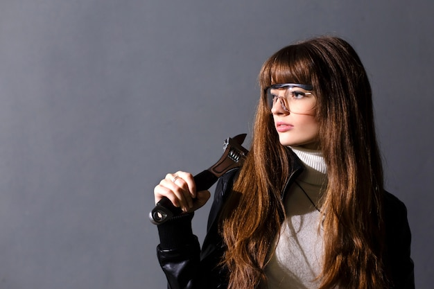 Young women in protective glasses with adjustable wrench on a dark