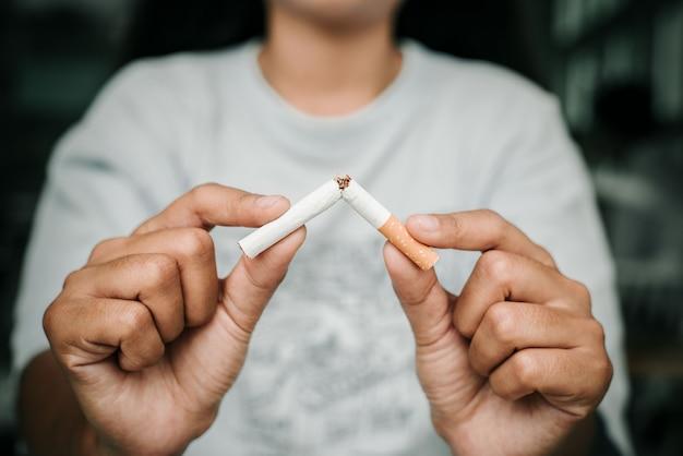 젊은 여성들은 금연과 건강한 생활 방식의 어두운 배경을 위해 담배 개념을 거부합니다. 또는 금연 캠페인 개념.