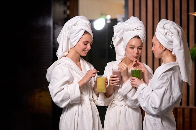 스파 시술 후 웰빙 센터에서 웰빙 주말에 웰빙 주말 동안 가운에 수분이 많은 음료 스무디를 마시고 휴식을 취하고 이야기하는 젊은 여성