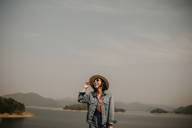 Young women relaxing on lake. he wearing sunglasses and hat.