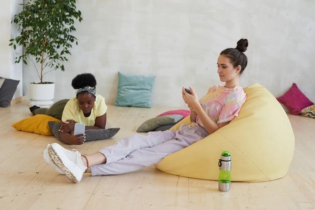 Молодые женщины отдыхают в креслах и общаются в интернете с помощью мобильных телефонов после тренировки в клубе здоровья