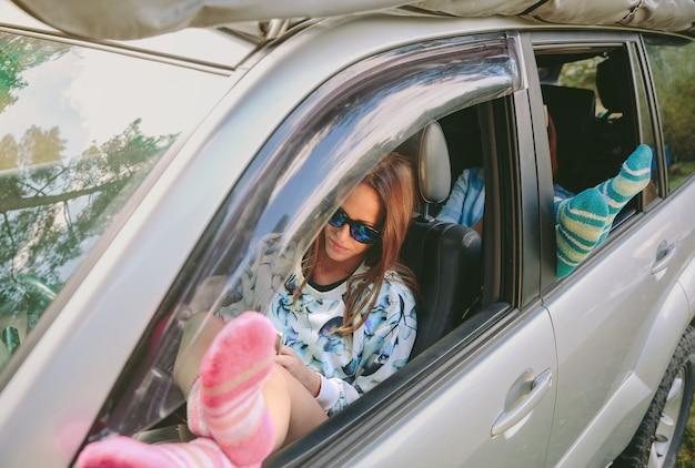 開いた窓の車の上で彼女の足で休んでいる若い女性。旅行とリラックスタイムのコンセプト。