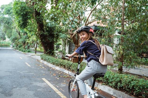 道路で折りたたみ自転車に乗る若い女性