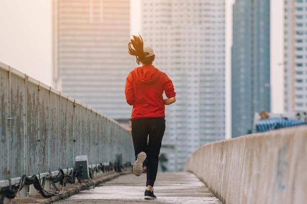 路上で若い女性ランナーが市の道路で運動をしている。スポーツ、人々、運動、ライフスタイルコンセプト