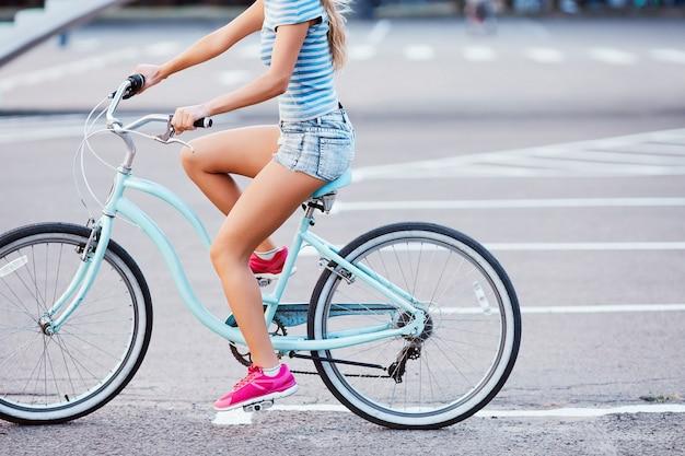 공원에서 복고풍 자전거를 타고 분홍색 운동화를 입고 젊은 여성의 황갈색 다리, 복사 공간, 모션 사진.