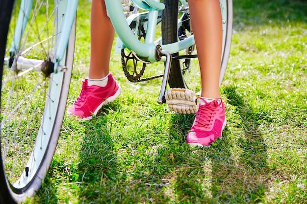 공원에서 푸른 잔디에 복고풍 자전거와 함께 서있는 분홍색 운동화를 입고 젊은 여성의 황갈색 다리 공간을 복사합니다.