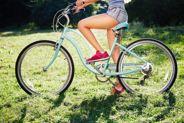공원에서 푸른 잔디에 복고풍 자전거와 함께 서있는 반바지 핑크 운동화를 입고 젊은 여성의 황갈색 다리 공간을 복사합니다.