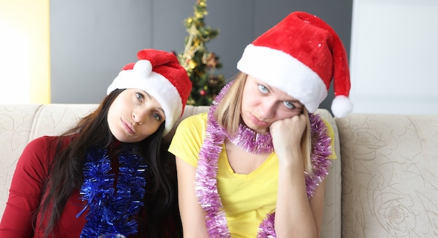 Young women in santa claus hat are boring on sofa at home