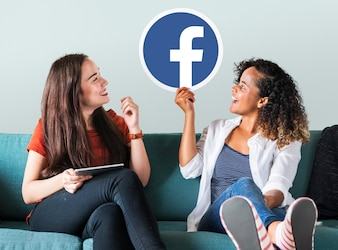 Young women showing a Facebook icon