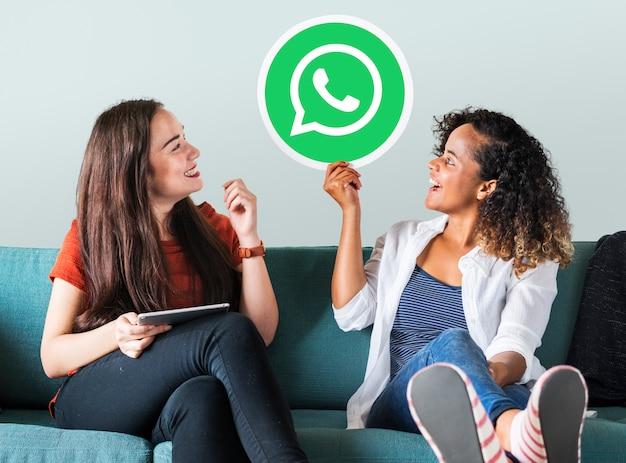 Whatsapp 메신저 아이콘을 보여주는 젊은 여성
