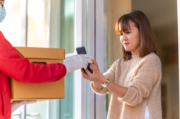 若い女性は、スマートフォン、宅配便の概念を介して商品を拾うために署名します