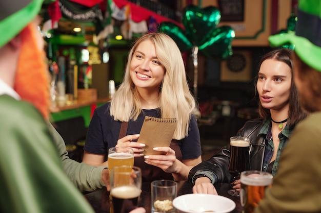 Молодые женщины сидят за столом, разговаривают с друзьями и пьют пиво во время празднования дня патрика в баре
