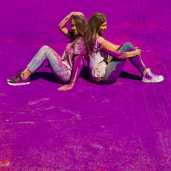Young women sitting back to back over the purple holi color