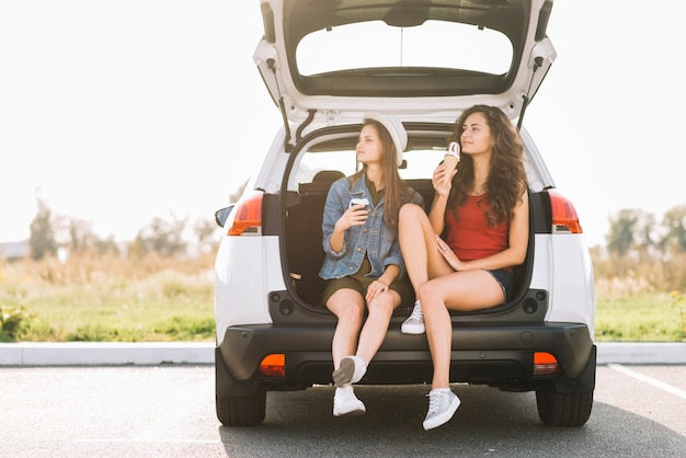 Young women sitting on car trunk